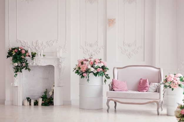 White textile classical style sofa in vintage room. flowers ob painted barrels Free Photo