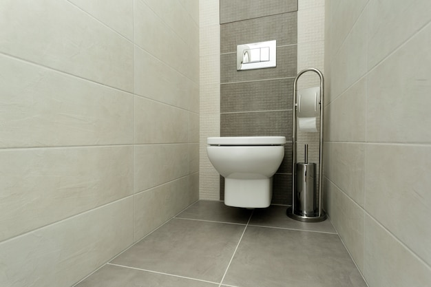 White toilet bowl in modern bathroom with paper holder and toilet brush. Premium Photo