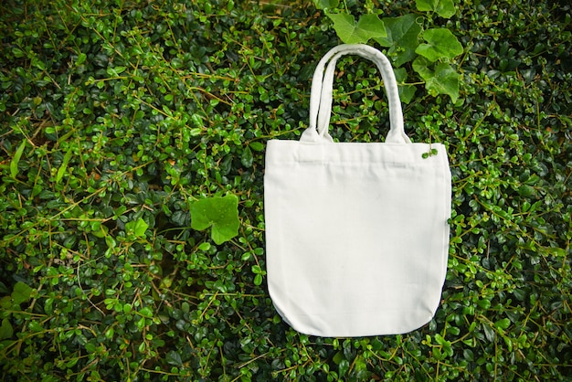 White tote canvas fabric eco bag cloth shopping sack on green leaf nature background Premium Photo