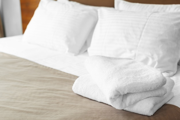White towel on bed in guest room for hotel customer Premium Photo