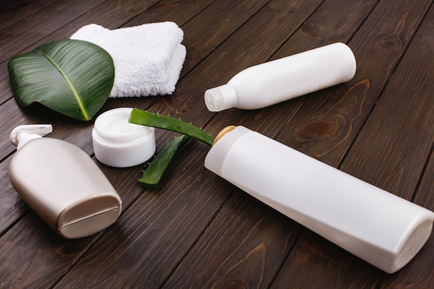 White towel, bottles of shampoo and conditioner lie on a table with green leaf and aloe Free Photo