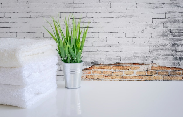 White towel and houseplant on white table with old brick wall Premium Photo
