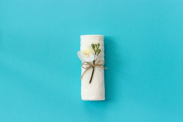 White towel roll tied with rope with sprig of orchid flower on blue paper background. Premium Photo