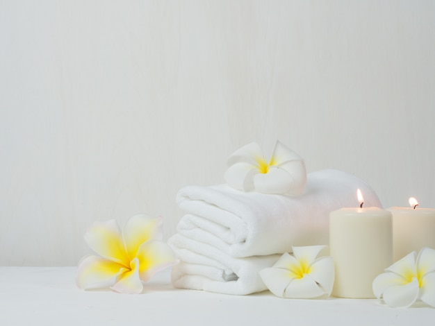 White towel with pink rose flower on the table Premium Photo