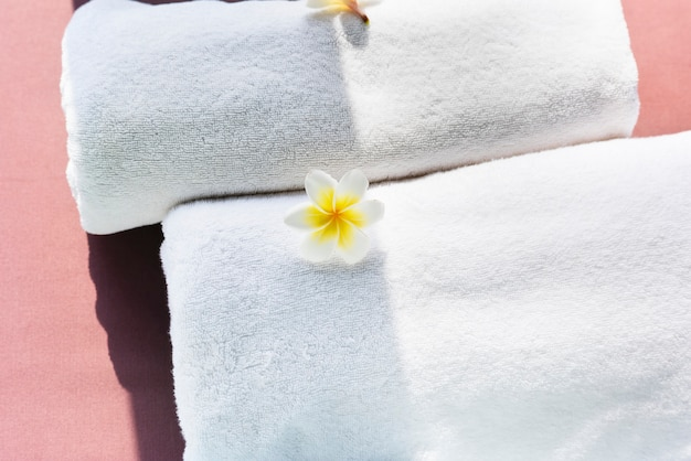 White towels decorated with plumeria flowers Free Photo