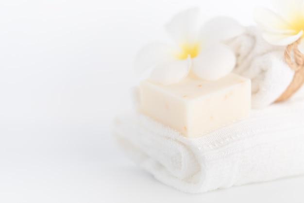 White towels,organic soap and plumeria flower over white Premium Photo