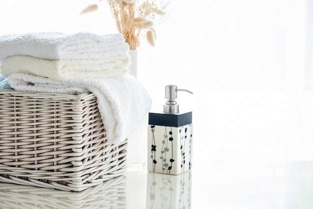 White towels in rattan basket on white table with bright room background Premium Photo