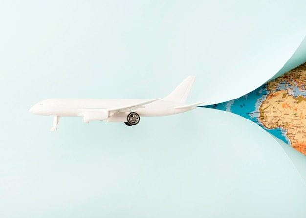 White toy plane with world map Free Photo