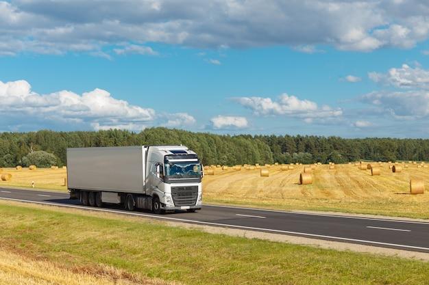 Белый трейлер на шоссе, на фоне желтого поля и голубого неба. есть место для рекламы Premium Фотографии