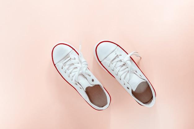 White trendy white sneakers on creamy peach background Premium Photo