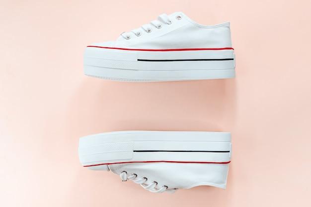 White trendy white sneakers on creamy peach Premium Photo