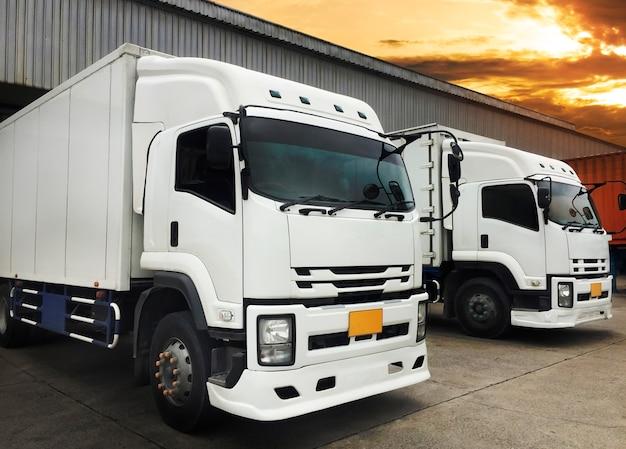 White trucks docking load cargo at warehouse, freight industry logistics transport Premium Photo