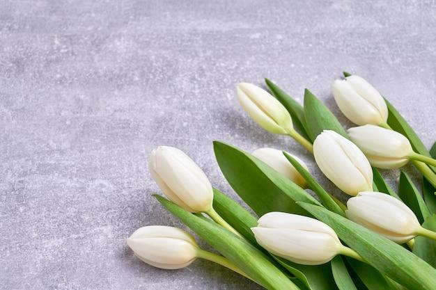 Белые тюльпаны на бетонном фоне. день рождения, день morthers, концепция дня святого валентина. праздничный фон, поздравительная открытка, копией пространства Premium Фотографии