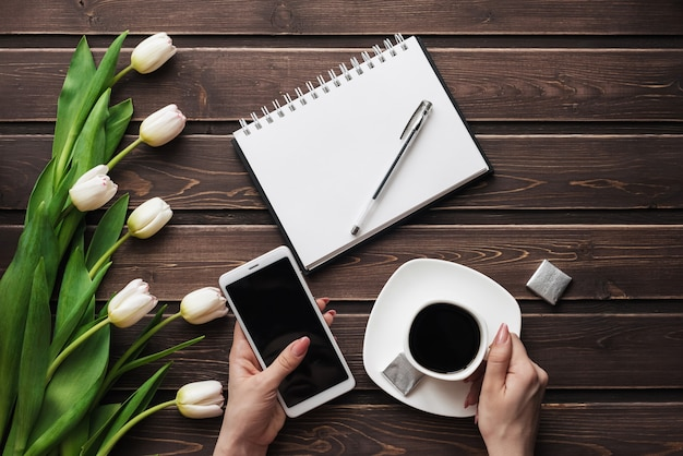 White tulips on a wooden table with an empty notebook, smartphone and a cup of coffee in women's hands Premium Photo