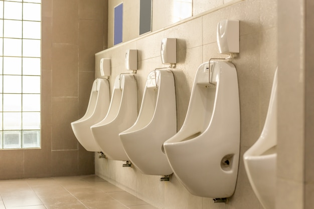 White urinals in a row in men public toilet. Premium Photo