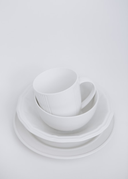 White utensils three plates and a cup on a white background Free Photo