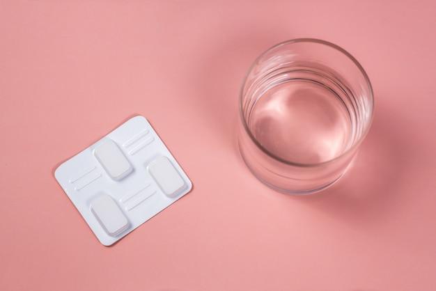 Белые вагинальные антибактериальные таблетки на розовом фоне. свечи замачивают в воде и вводят во влагалище для лечения кандидоза, молочницы, воспаления. эффективный современный препарат для лечения заболеваний Premium Фотографии