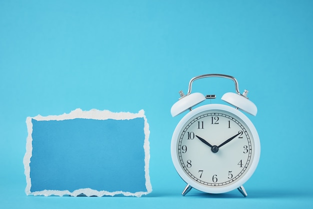 White vintage classic alarm clock with bells and empty torn paper sheet on blue Premium Photo