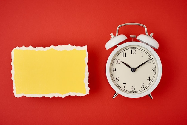 White vintage classic alarm clock with bells and empty torn paper sheet on red background.  design blank for time concept Premium Photo