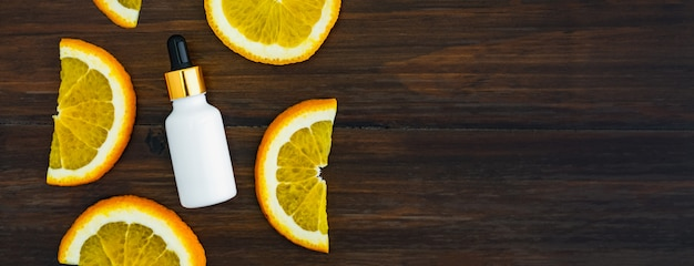 White vitamin c bottle and oil made from orange fruit extract, mockup of beauty product brand. top view on the wood background. Premium Photo