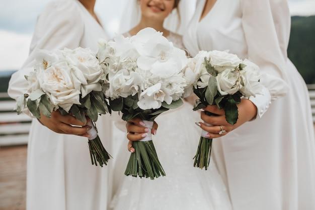 カラスと蘭が屋外の手で作られた花嫁とブライドメイドの白いウェディングブーケ 無料写真