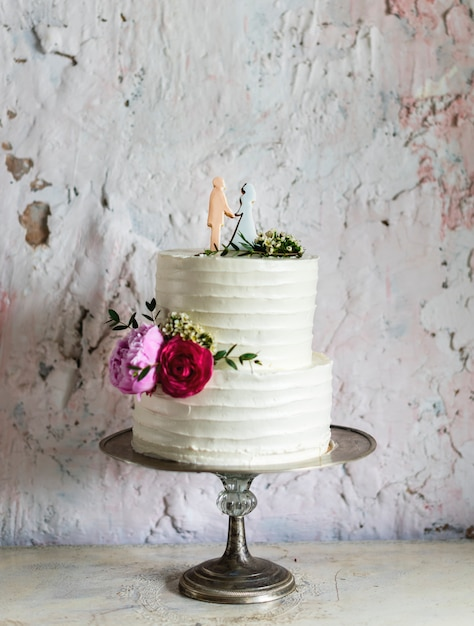 White Wedding Cake with Bride and Groom Figure Topper Free Photo