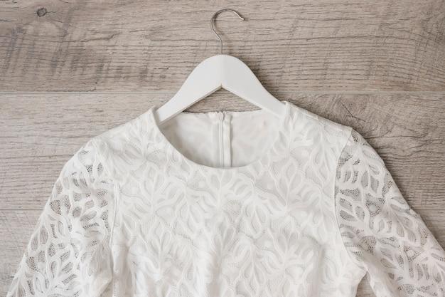 White wedding dress on coat hanger against wooden textured backdrop Free Photo