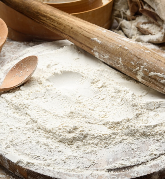 Белая пшеничная мука и деревянная скалка на доске, ингредиенты для выпечки, крупным планом Premium Фотографии
