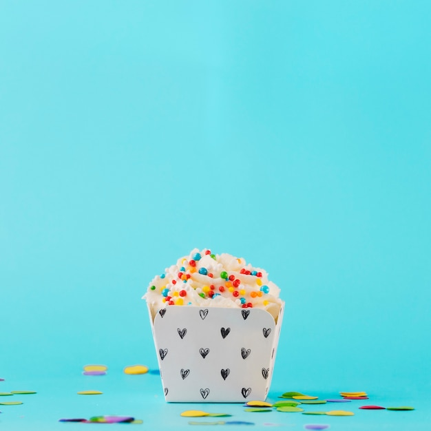 White whipped cream with colorful sprinkles and confetti against blue background Free Photo
