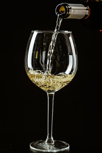 White wine being poured in a wine glass Premium Photo