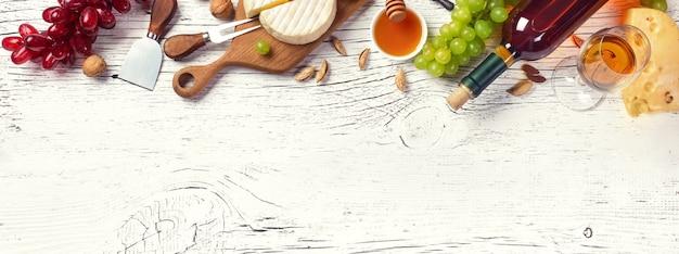White wine bottle, grape, honey, cheese and wineglass on white wooden board Premium Photo