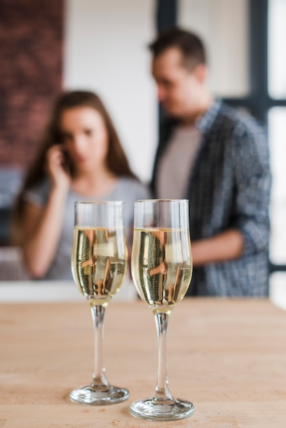 White wine glasses and couple at home Free Photo