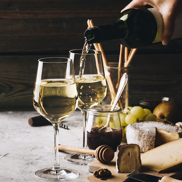 White wine pouring into glasses with charcuterie assortment Premium Photo