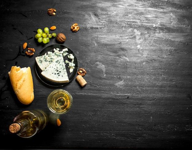 프렌치 블루 치즈와 견과류를 넣은 화이트 와인. 검은 나무 보드에 프리미엄 사진