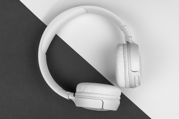 White wireless headphones lie on a black and white background Premium Photo