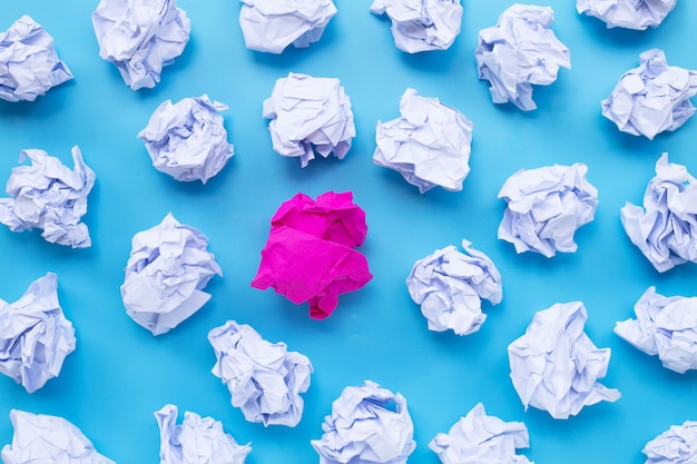 White with pink crumpled paper balls on a blue background. Premium Photo