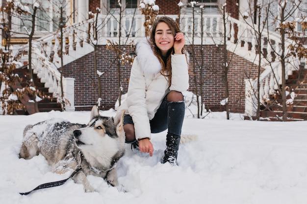 Белая женщина с удивительной улыбкой позирует со своей собакой во время зимней прогулки во дворе. на открытом воздухе фотография веселой дамы в рваных джинсовых штанах, сидящей на снегу с ленивым хаски. Бесплатные Фотографии