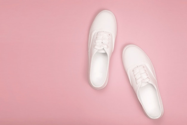 White women's sneakers on a pink background. flat lay, top view and copy space in minimalist style. concept of fashion blog,soft focus Premium Photo