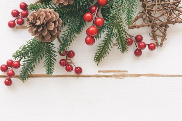 松の葉、松ぼっくりや針葉樹の円錐形、赤いヒイラギのボール、クリスマスコンセプトの木製の星と白いウッドテクスチャ。トップビューフラットで木の板の背景は、クリスマスの壁紙のコピースペースを置きます。 Premium写真