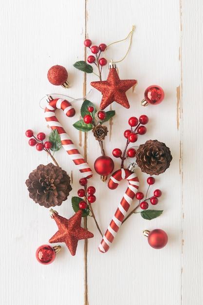 Белая древесина с сосновыми шишками или шишками, красные шарики падуба, звезда с блестками, конфета и безделушка в рождественской концепции. вертикальная планка фон в плоском виде сверху кладут копию пространство для рождественских обоев Premium Фотографии