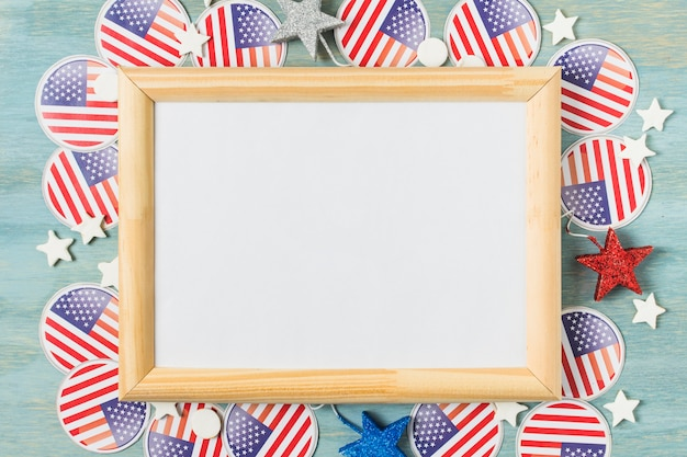 White wooden board over the usa flag badges and stars on blue textured backdrop Free Photo