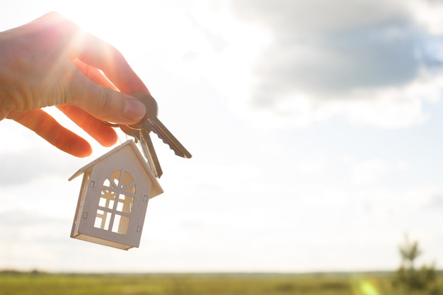 Premium Photo White Wooden Figure Of A House And Keys In Hand