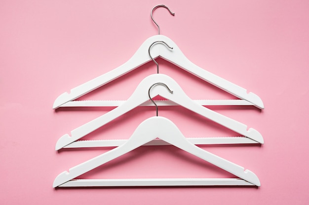 White wooden hangers on pink Premium Photo