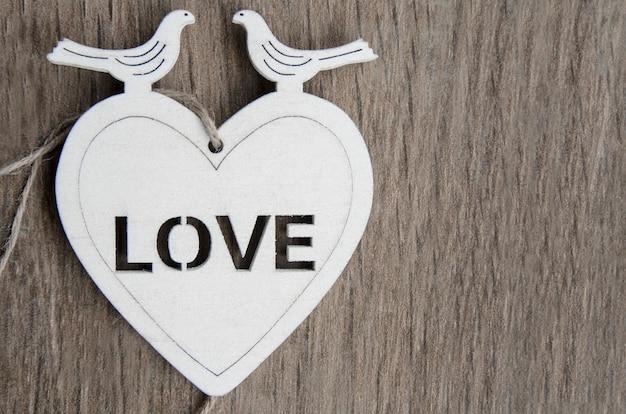 Белое деревянное сердце с двумя голубями на вершине. винтажное украшение открытки Premium Фотографии