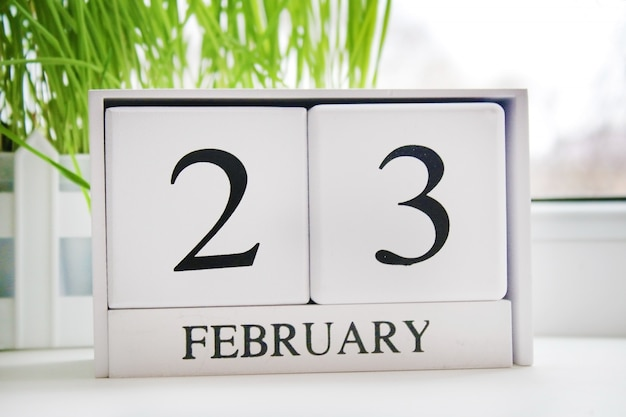 White wooden perpetual calendar with the date of february 23 at the window. Premium Photo
