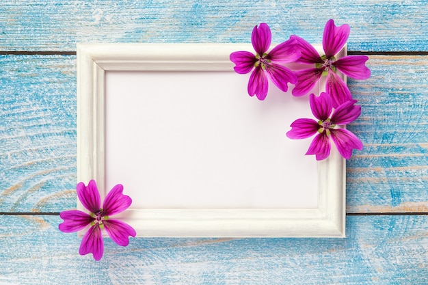 White wooden photo frame with purple flowers on pink paper background. Premium Photo