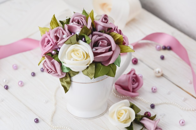 White wooden table with pink flowers, ribbons and beads. wedding style Premium Photo
