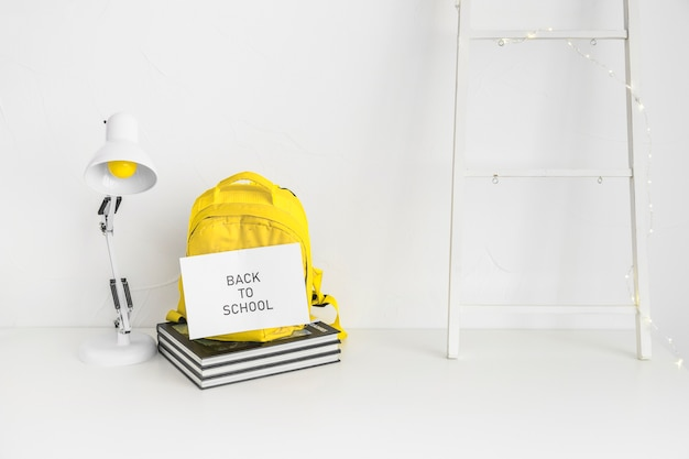 White workspace for pupil with yellow backpack Free Photo