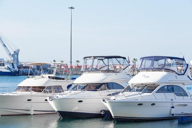 Белые яхты в порту. лодки в гавани голубой воды. Premium Фотографии