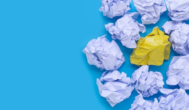White and yellow crumpled paper balls on a blue background. Premium Photo